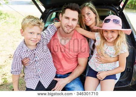 Family with two children in the car on vacation in summer