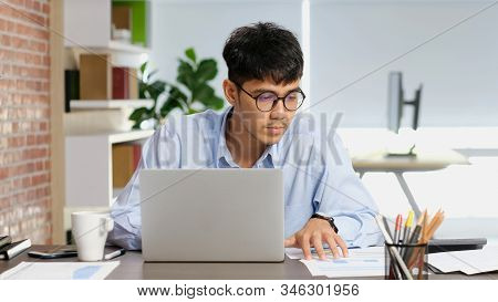 Asian Man At Office, Young Asia Businessman Concentrate On Paper Work While Working With Laptop Comp