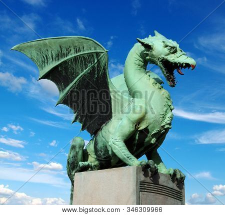 Sculpture of dragon on Dragon bridge on beautiful cloudy sky background in Ljubljana, Slovenia