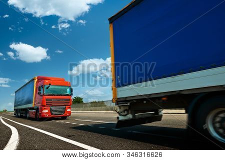 Red and blue trucks is on highway - business, commercial, cargo transportation concept