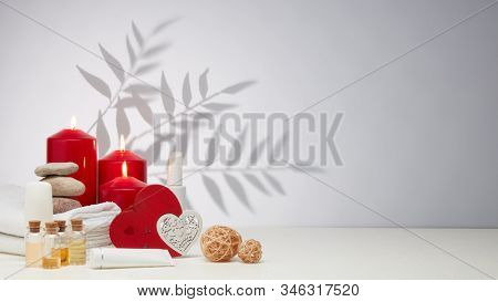 Spa still life with creams, essential oils, burning red candles, hearts on light background with shadow from plant. Healthy lifestyle, body care, Spa treatment. Valentine's Day. Honeymoon. Wedding