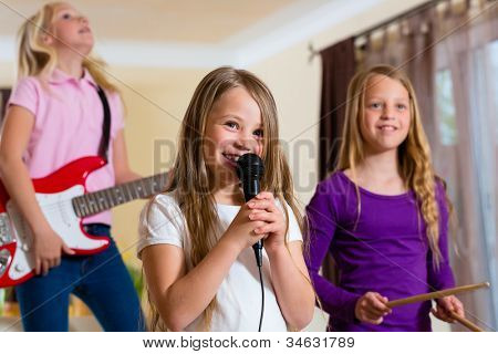 Children - three sisters - playing in a band making music
