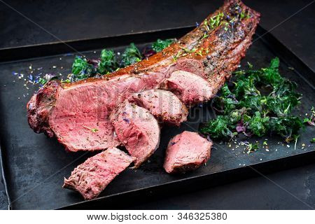 Barbecued dry aged venison tenderloin fillet steak and saddle natural with kalette offered as closeup on a rustic board