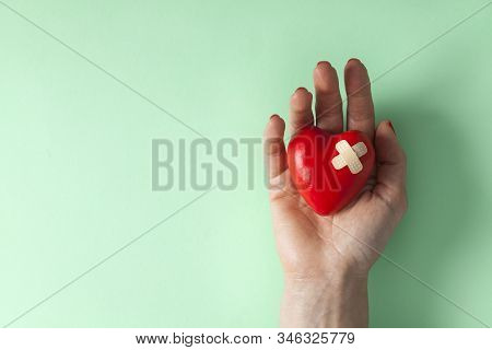 Woman Hand Holding A Broken Heart. Red Broken Heart With A Aid Plaster
