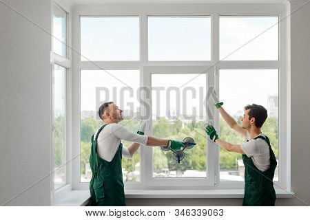Two Window Installers Replacing A Window In The Living Room