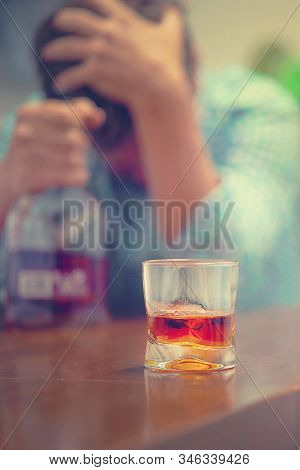 Man With Bottle Of Whiskey On The Kitchen. The Concept Of Drunkenness And Alcoholism. Alcoholic Fath