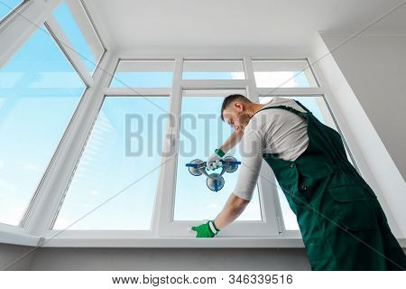 Professional Repairman Installing A White Corner Window