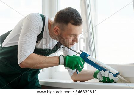 Focused Man Is Applying Sealant Using A Caulking Gun