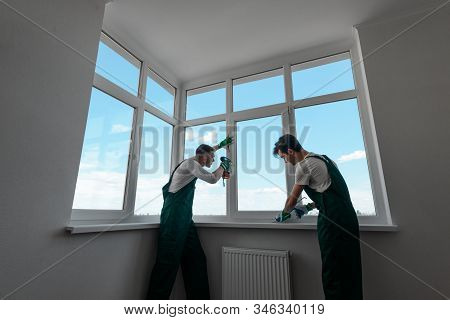 Two Men Are Repairing Customers Home. Fixing A Window Handle
