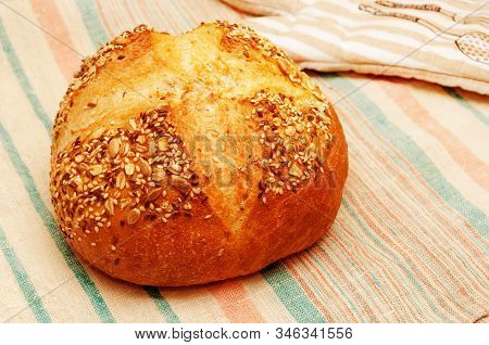 Freshly Baked Golden Multigrain Bread. Round Loaf With Crisp Sprinkled With Seeds Of Flax, Sesame, S