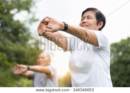 Asian Senior People Stretching Their Arms Before Exercising. Copy Space. Good Health.