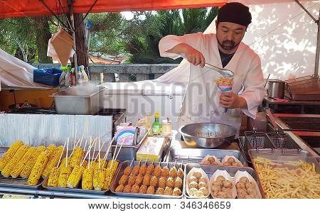 Miyajima Island, Japan - 13 April, 2019: Man Preparing Typical Fried Food. The Japanese Delicacies I