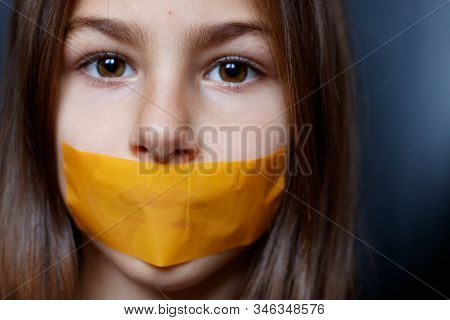 Unhappy Girl With Sticky Tape Over Her Mouth. Violation Of Human Rights. Kidnapping.