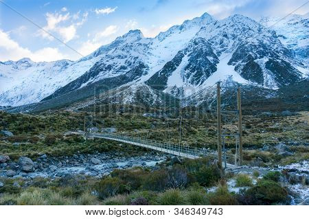 Hiking In Moutnains Landscape With Suspension Bridge And Snow Covered Mountains. Hooker Valley At Ao