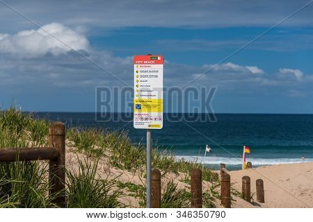 Wollongong, Australia - September 20, 2015: Warning Sign On Wollongong City Beach With Sand Dunes, O
