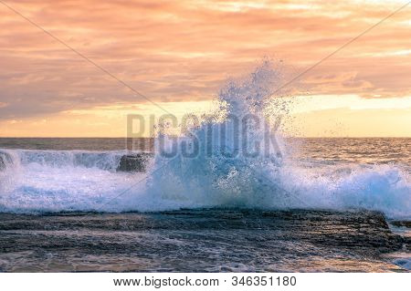 Strong Big Wave Crushing Over Rocks With Beautiful Sunset Sky On The Background. Powerful Wave Drama