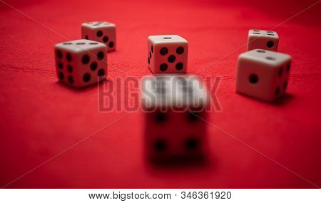 Hand Throwing Dice, Hoping For The Best Odds. Six Dice On Red Background