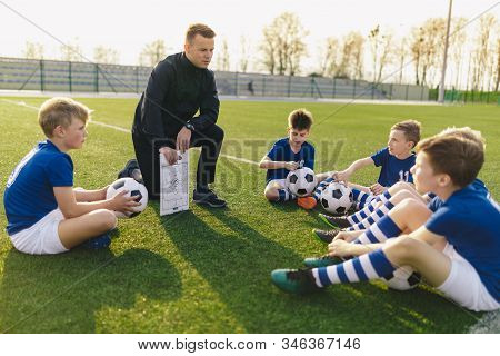 Group Of Young Boys Sitting On Sports Grass Field Witch School Coach. Kids Listening Coach's Tactic