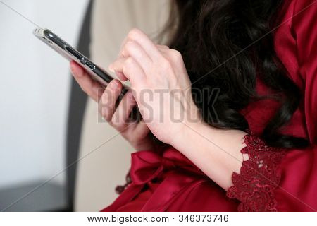 Woman Using Smartphone At Home In A Bed, Girl In Red Lace Robe With Mobile Phone In Hands. Concept O