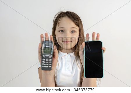 Teenager Girl With Old Nokia Phone And Iphone. Focus On The Girl. The Question Of Choosing A Phone F
