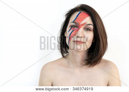 red and blue lightning bolt on her beautiful face. Beautiful girl with original make-up on a white background. Studio photo. poster