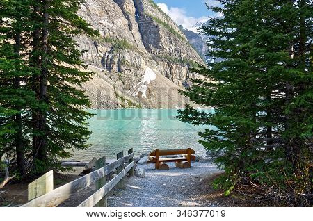 Turquoise Waters Of Beautiful Moraine Lake. Snow-covered Rocky Mountains In Summer Day. Log Bench On