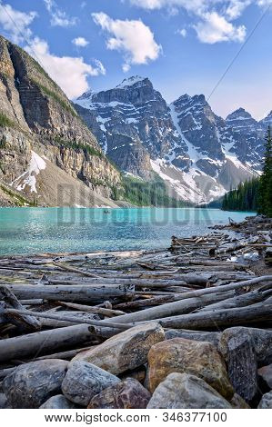 Turquoise Waters Of Beautiful Moraine Lake. Snow-covered Rocky Mountains In Summer Day. Banff Nation