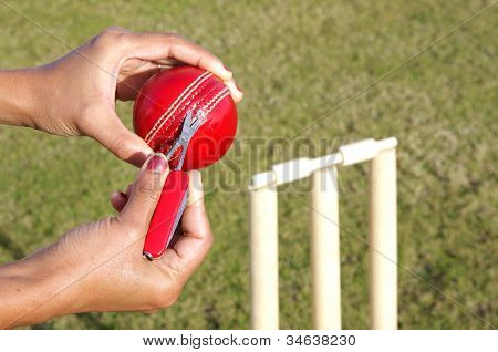 Umpire cutting the ripped thread from a cricket ball