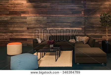 Interior design concept of living room with lacquered wooden wall, dark corner sofa and round colorful ottomans and bright carpet on the floor. 3d Rendering.
