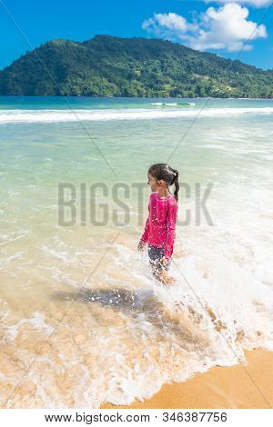 Little Girl Standing In Maracas Bay Beach Trinidad And Tobago Having Fun Splashing In The Waves Look