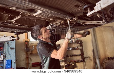 Close Up View Of Car Mechanic Making Effort For Screwing Up Auto Detail. Checking And Servicing Car