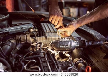 Car Mechanic Repairing Diesel Engine With Screwdriver And Flashlight Helping In Garage Workshop. Clo