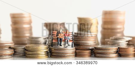 Miniature People: Elderly People Sitting On Coins Stack. Retirement Planning. Money Saving And Inves