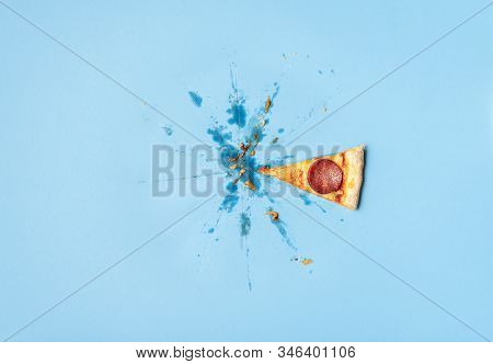 Single Slice Of Pizza Pepperoni And Leftovers Crumbs And Grease Traces On Blue Background. Last Piec