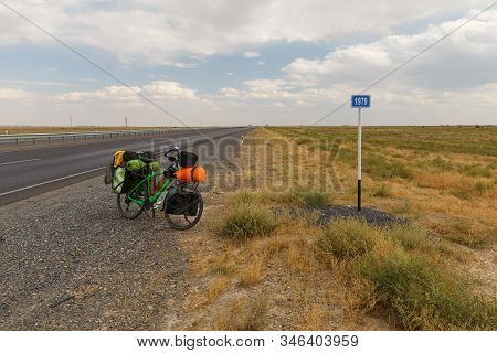 Bicycle For A Traveler Stands On The Road Near A Kilometer Sign, Kazakhstan