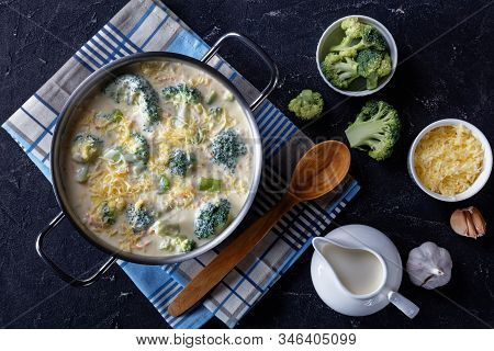 Broccoli And Cheddar Cheese Soup In A Saucepot On A Concrete Table With Grated Cheese And Fresh Crea