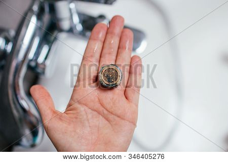 Repair Of The Crane Aerator. Purification Of The Aerator From Deposits. The Hand Of The Girl Holds I
