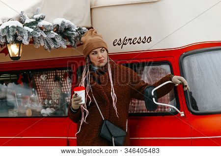 A Street Photo Of A Young Woman In A Coat And Cap Walking Down The Street With A Cup Of Coffee In He