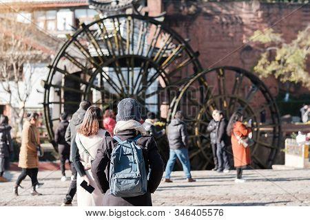 Young Woman Traveler Traveling At Giant Water Wheels In Lijiang Old Town, Landmark And Popular Spot