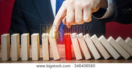 Businessman Restarts The Process Of Falling Dominoes. Start Work After Stopping. Continuation Of Wor