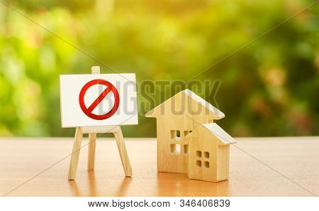 Wooden Houses And An Easel With A Red Prohibition Sign No. Inaccessibility And Lack Of Housing, Defi