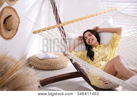 Young Woman Relaxing In Hammock At Home
