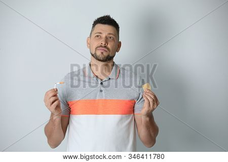 Thoughtful Man With Nicotine Patch And Cigarette On Light Grey Background