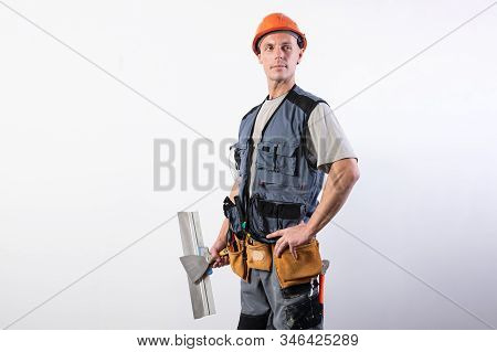 Proud Builder With A Trowel. In Work Clothes And Hard Hat. On A Light Gray Background.