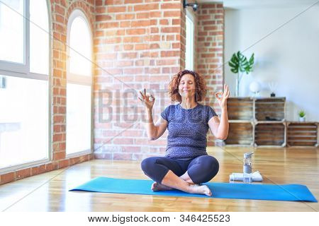 Middle age beautiful sportswoman wearing sportswear sitting on mat practicing yoga at home relax and smiling with eyes closed doing meditation gesture with fingers. Yoga concept.