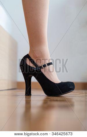 Caucasian Female Legs Close Up Shot Wearing Black High Heel Shoes Inside On Wooden Tile Pavement.