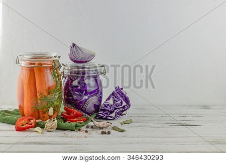 Two Glass Jars Of Fermented Red Cabbage, Onions, Carrots. Vegetables On A Light Background. Using Te