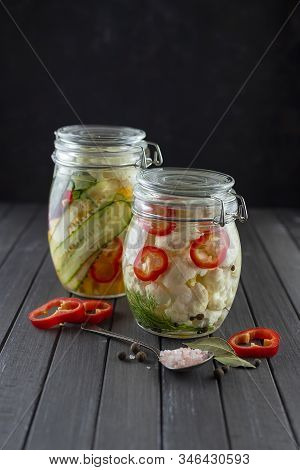 Glass Jars Of Fermented Cauliflower, Cucumbers, Carrots, Chili Pepper, Spices, Salt. Vegetables On A
