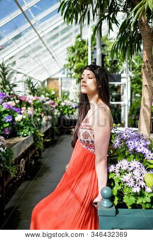 Beautiful Woman in Spring Time with Colorful Flowers in a Nursery