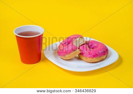 Two Sweet Half-eaten Pink Doughnuts On A White Plate Isolated On A Yellow Background. Red Disposable